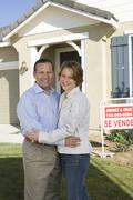Stock Photo of Couple Embracing In Front Of New House