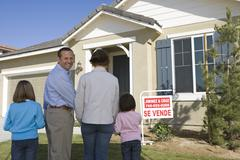 Stock Photo of Family Standing Near For Sale Sign