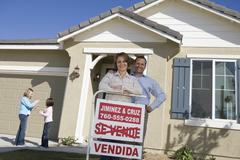 Stock Photo of Happy Family Outside Home With Sold Sign
