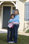Sisters Embracing In Front Of House - stock photo