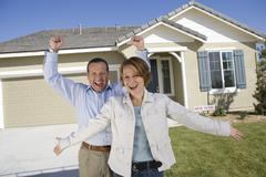 Stock Photo of Excited Couple In Front Of New House