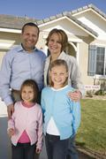 Stock Photo of Happy Family In Front Of New House
