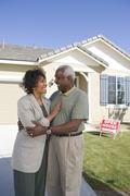 Couple Standing In Front Of House For Sale - stock photo
