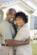 Couple Embracing In Front Of New House - stock photo
