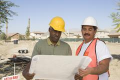 Architects With Blueprint At Construction Site Stock Photos