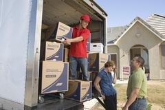 Delivery Man And Couple Unloading Moving Boxes From Truck Stock Photos