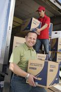 Stock Photo of Man With Worker Unloading Truck Of Cardboard Boxes