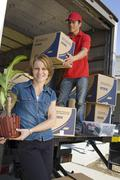 Woman With Delivery Man Unloading Moving Boxes From Truck - stock photo