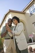 Couple Holding Key In Front Of New House - stock photo