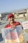 Happy Deliveryman Carrying Container - stock photo
