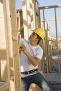 Worker Measuring Timber At Construction Site - stock photo