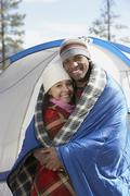 Young Couple Wrapped In Blankets At Campsite - stock photo