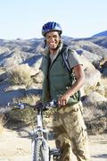 Young Man Standing With Mountain Bike Against Hills - stock photo