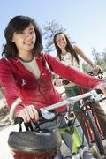 Stock Photo of Female Friends Riding Bicycle