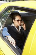 Businesswoman Using Cellphone In Taxi - stock photo