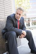 Businessman Sitting On His Briefcase - stock photo