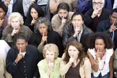 Group Of People With Finger On Lips - stock photo