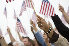 Hands Raising American Flag Stock Photos