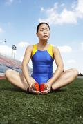 Stock Photo of Female Athlete Exercising On Field