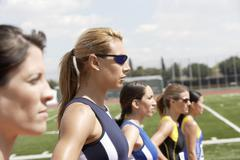 Female Athletes Standing In Line On Field - stock photo