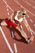 Stock Photo of Male Athlete Stretching On Racetrack