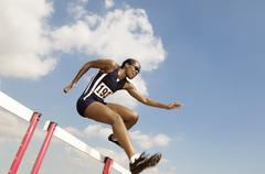 Female Athlete Jumping Hurdle - stock photo