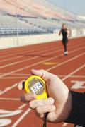 Stock Photo of Hand Holding Stopwatch With Runner On Race Track