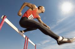 Male Athlete Jumping Over A Hurdles Stock Photos