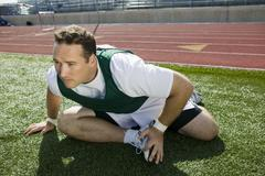 Stock Photo of Athlete Stretching On Track