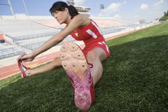 Stock Photo of Athlete Stretching On Field