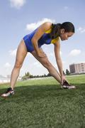 Stock Photo of Female Asian Athlete Working Out On Field
