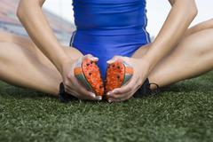 Stock Photo of Female Athlete Exercising On Grass