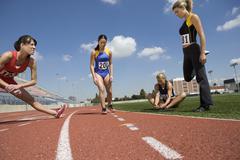 Female Athletes Stretching Before Race Stock Photos