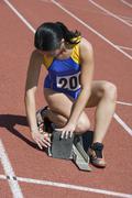 Stock Photo of Female Athlete Adjusting Starting Block