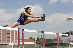 Female Athlete Jumping Over A Hurdles Stock Photos