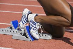 Female Runner On Starting Blocks - stock photo