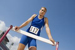 Female Athlete Standing At Hurdle Stock Photos