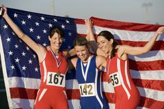 Female Athletes With American Flag And Medals - stock photo