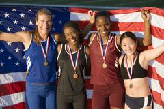 Multiethnic excited female athletes with American flag and medals - stock photo