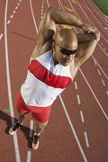 Male Athlete Stretching On Race Track Stock Photos