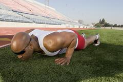 Male Athlete Doing Push-Up Before Race - stock photo