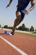 Male Runner Beginning Race From Starting Blocks - stock photo