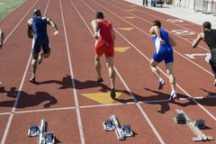 Male Athletes Running From Starting Block - stock photo