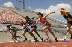 Female Athletes Taking Off From Starting Blocks - stock photo