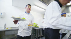 Team of professional chefs preparing food in a commercial kitchen Stock Footage