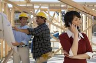 Stock Photo of Woman On Call With Contractors In Background