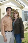 Happy Couple Standing Outside Their New House - stock photo