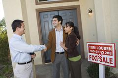 Agent Shaking Hands With Couple - stock photo
