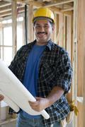 Male Architect Holding Unrolled Blueprint - stock photo