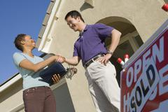 Female Estate Agent Shaking Hands With Man - stock photo